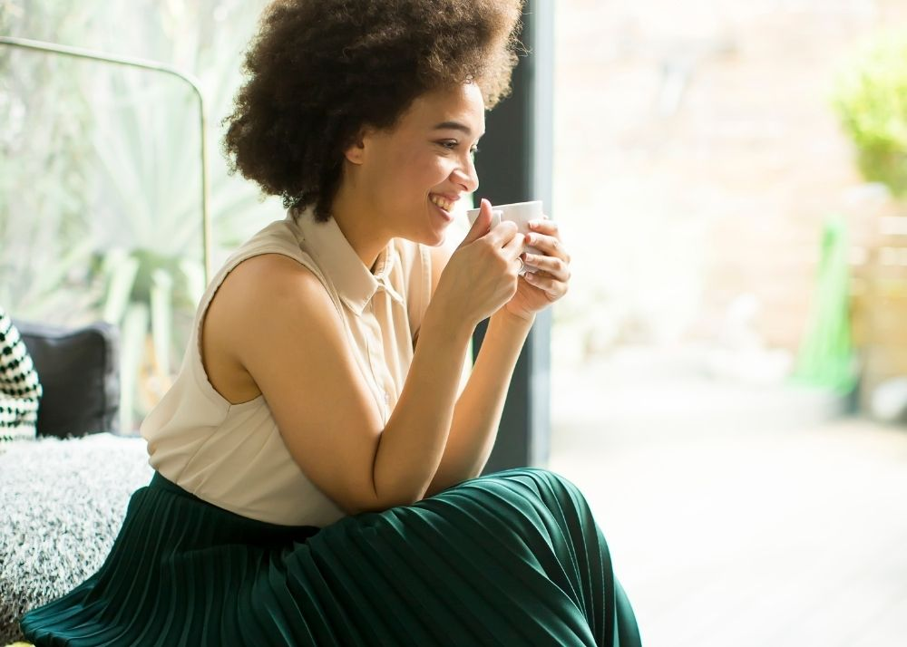 Woman sitting down drinking cup of Annique Rooibos tea in Summer