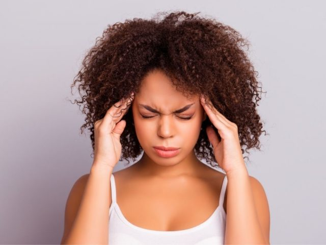 African American Woman with headache pressing hands against head