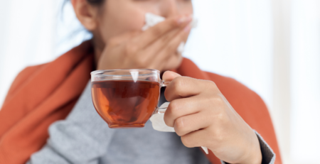 Sick woman holding cup of Rooibos tea and tissue