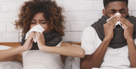 Couple sick in bed with cold and flu