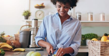 Healthy African American Woman making lunch in kitchen