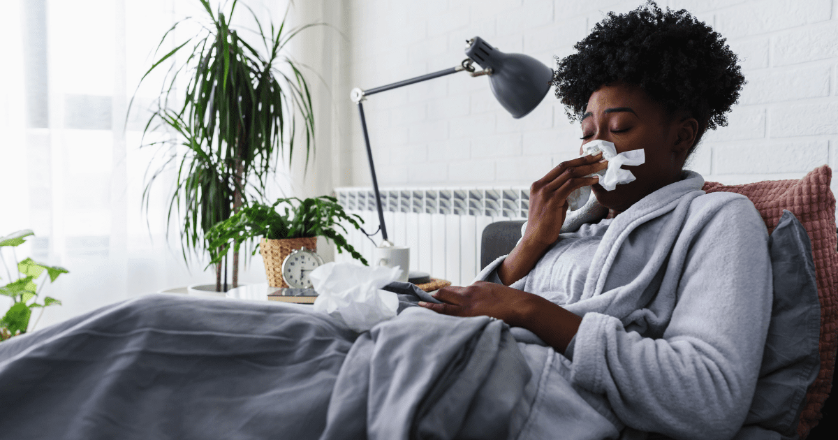 Woman in bed sick with flu blowing nose